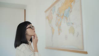 Side view, attractive young and beautiful brunette girl in glasses talks and points travel routes on big world map poster hanged on white wall, plans her destination points in next adventure