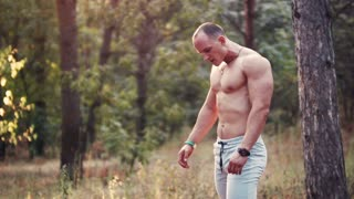 Side view of handsome topless bodybuilder doing biceps curls with log in forest