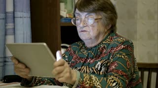 Side view of senior woman scrolling photos on the tablet computer and telling something