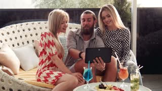 Side view on man with pair of girlfriends using tablet computer to make self portraits while seated in large chair in front of snacks and drinks at lounge