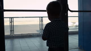 Silhouette of a young boy looking through a window in the airport to the airplanes in the landing strip