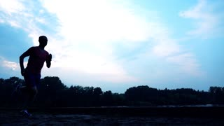 Silhouette of athletic man running on sandy riverside in the evening, 240 fps. Super slow motion steadicam video