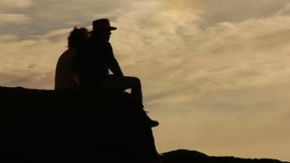 Silhouette Of Couple Sitting On Rock