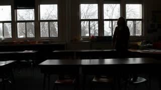 Silhouette Of Teacher Putting Up Chairs In Classroom