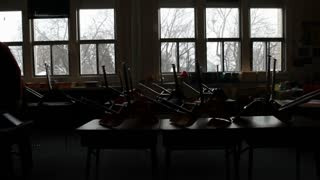 Silhouette Of Teacher Taking Down Chairs In Class