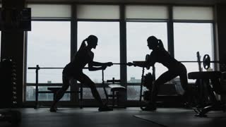 Silhouette of two womans pulling a rope in a sport fitness gym