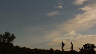 Silhouettes Of Couple Hiking Against Sunset Sky