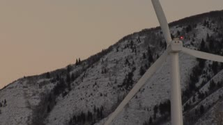 Single windmill with snowy mountains in the background