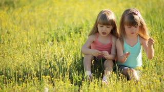 Sisters sitting on grass and talking about something