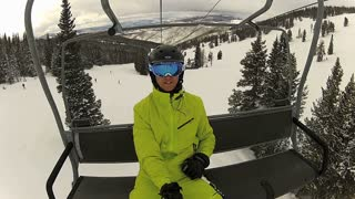 Skier on Lift with Mountains Background