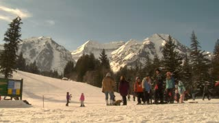 Skiers At Base Of Hill Gather, Family Glides Past
