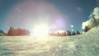 Skiers ski through sun towards camera