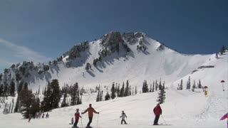 Skiers Start Down Gentle Hill, Mountains Above