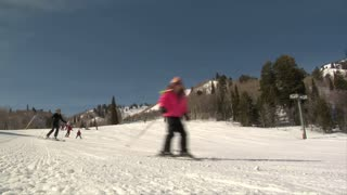 Skiing Family Glides Past Camera On Snowy Hill