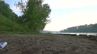 Slender brunnete girl running on sandy summer riverside. Super slow motion crane video