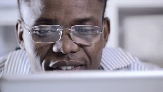 slider shot of African American with reflective spectacles viewing tablet computer