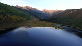 Slow flight over reflective lake at dusk in Colorado Rocky Mountains