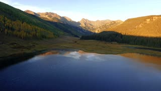 Slow flight over reflective lake at sunset in Colorado Rocky Mountains