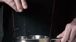 Slow mo chef throws a pinch seasoning in a metal pan