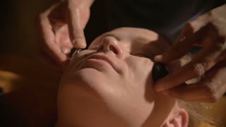 Slow motion and close-up shot of a young woman getting professional facial massage with usage of hot stones in day spa. She relaxing with closed eyes