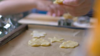Slow motion and close-up shot of female hand putting star cookie dough on the baking tray with other cutouts. Home-baked treats