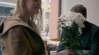 Slow motion clip of a young man and woman looking at each other with love during the date in cafe. Girl holding white flowers. Romantic moments
