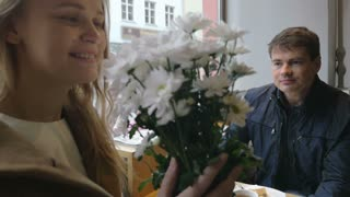 Slow motion clip of a young woman and man having a date in cafe. She enjoying the smell of presented flowers while he looking at her with love