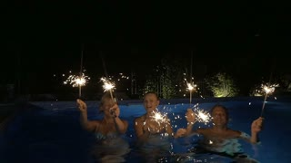 Slow motion clip of two happy women and a man dancing with sparklers in the swimming pool at night. Christmas and New Year celebration