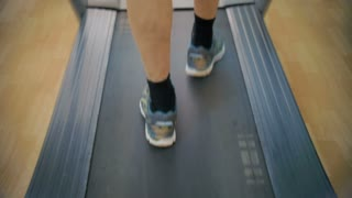Slow motion close-up shot of male feet walking on treadmill. Every time he coming to the gym he having some cardio