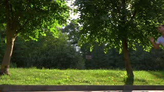 Slow motion dolly shot of athletic man in white tshirt running in park against sun and trees