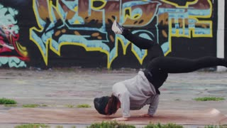 Slow motion Female Break Dancer Performing in front of Graffiti Wall