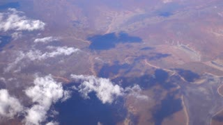 SLOW MOTION: Flying high above white clouds over the vast brown sand desert
