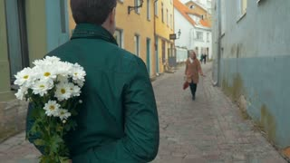 Slow motion of a happy girl running to her boyfriend and he meeting her with a bunch of flowers, she embracing and kissing him. Romantic moments together
