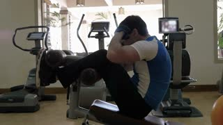 Slow motion of a man exercising on modern equipped fitness center. He doing sit-ups on abdominal bench and then stopping for a break