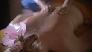 Slow motion of a woman with pink flower in hair receiving professional back massage in beauty spa. Body care and relaxation