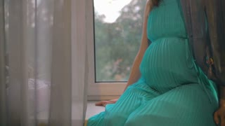 Slow motion of a young pregnant woman in turquoise blue dress sitting on the windowsill at home and embracing her belly. Expecting a baby is a wonderful time