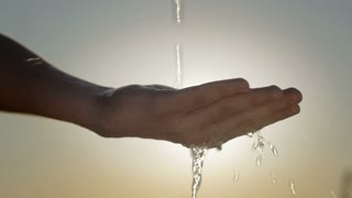 Slow motion of clean water falling on a human hand against the sun. Source of life.