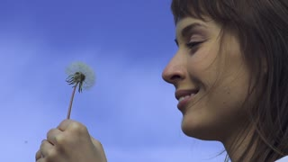 Slow motion of Dandelion being blown by a young happy woman. Slow motion 240 fps. HD 1920X1080. Dandelion seeds are being blown by a young funny woman on a green grass background.