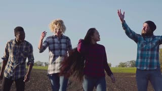 Slow motion of excited group of four teenagers in empty cultivated field rural landscape under the blue sky at sunset in evening jumping