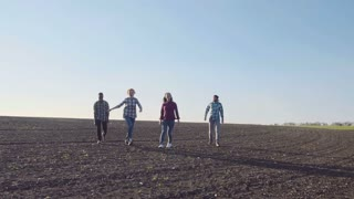Slow motion of excited group of four teenagers in empty cultivated field under the blue sky jumping