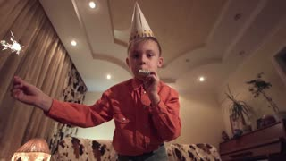 Slow motion of little boy in Birthday cap holding sparkler and blowing whistle at camera in modern room