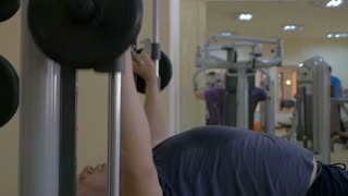 Slow motion of mature man working on chest press exercise machine in fitness center. Getting fit taking efforts