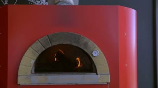 Slow motion of placing pizza in wood-fired stove with pizza peel