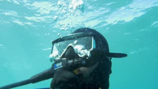 Slow motion of scuba diver underwater close to surface. When he looking up sun reflecting in his mask