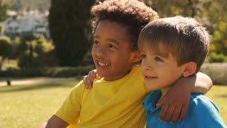 Slow motion of two boys sitting on grass together in park.