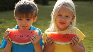 Slow motion of two children eating water melon in park