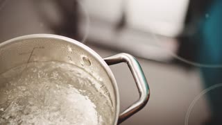 Slow motion pan over boiling water in kitchen