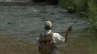 Slow Motion Pull Out Shot Of Fly Fisherman And Red Rock Cliffs