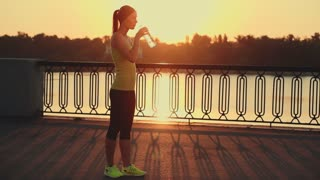 Slow motion: running woman. Runner is jogging in sunny bright light. Female fitness model training outside in the city on a quay. Sport lifestyle. Filmed at 240 fps.
