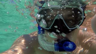 Slow motion selfie shot made by white man while snorkel diving.